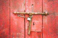 Porta di legno con struttura rustica di colore rosso della catena di serratura vecchia fotografia stock libera da diritti