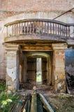 Porta di legno con un balcone con le inferriate di legno nelle rovine di vecchia chiesa del mattone Immagine Stock