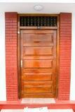 Porta di legno decorata chiusa di una casa dell'alta società, accentata con un corteggiare Fotografia Stock Libera da Diritti
