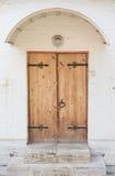 Porta di legno decorata storica in un'entrata di pietra Fotografie Stock