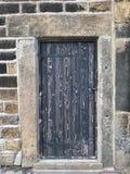 Porta di legno nera antica con vecchia pittura di pelatura sbiadita nel telaio di pietra pesante con un bullone chiuso e le cerni Fotografia Stock