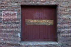 Porta di legno rustica circondata invecchiando muro di mattoni immagine stock libera da diritti