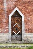 Porta di legno scura in muro di mattoni rosso, rinascita gotica Fotografie Stock