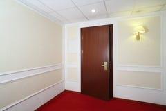 Porta di legno socchiusa, tappeto rosso sul pavimento Fotografie Stock