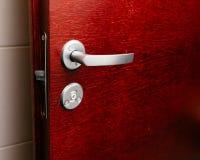 Porta di mogano di legno rossa con la maniglia immagini stock