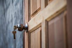 Porta do botão, a chave e a de madeira no fundo cinzento foto de stock