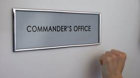 Porta do escritório do comandante, mão que bate o close up, autoridade militar, liderança foto de stock
