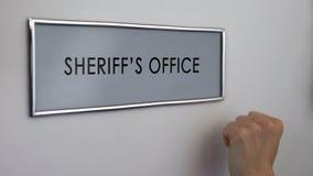 Porta do escritório do xerife, mão que bate, agente da autoridade, prevenção da criminalidade fotografia de stock