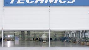 Porta do obturador do rolo e assoalho concreto do hangar do aeroporto e do fundo do avião Hangar do aeroporto da parte externa co filme