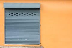 Porta do obturador do rolo na parede amarela Fotografia de Stock