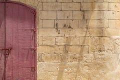 Porta dobro vermelha na parede amarela da pedra calcária foto de stock