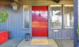 Porta e decoração vermelhas bonitas do Natal com a casa de madeira cinzenta fotos de stock royalty free
