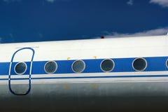 Porta e janelas velhas de aviões do passageiro contra o fundo do céu azul Imagem de Stock