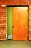 Porta e tijolos de madeira alaranjados fotografia de stock royalty free