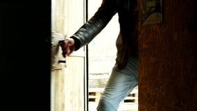 Porta entrante dell'uomo Il motociclista viene in garage Chiuda su della porta entrante nello scuro video d archivio