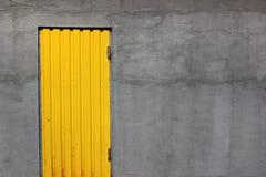 Porta fechado amarela brilhante em uma parede cinzenta Fotografia de Stock Royalty Free