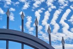 Porta forgiata contro il cielo blu con le linee di nuvole fotografia stock libera da diritti