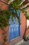 Porta greca dipinta blu sulla parete arancio Immagine Stock