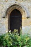 Porta laterale della chiesa con i fiori selvaggi Fotografie Stock