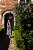 Porta lilás da parede do syringa do sol da mulher, Groot Begijnhof, Lovaina, Bélgica imagens de stock