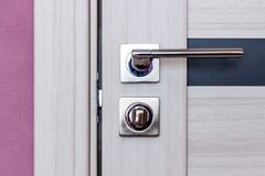 Porta moderna de madeira, botão de porta inoxidável ou punho na porta de madeira na iluminação bonita imagem de stock royalty free