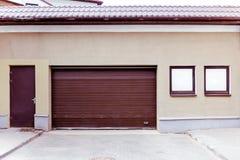 Porta ondulada marrom fechado da garagem do metal com entrada e windo Imagens de Stock Royalty Free
