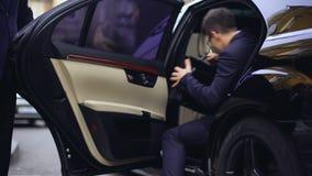 Porta personale di sedile posteriore di apertura dell'autista in automobile per il giovane riuscito uomo d'affari stock footage
