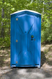 Porta Potty. A blue porta potty located on the wooded hiking trail Stock Photo
