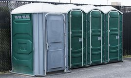 Porta potty in parking lot. Green and gray potties set up in a parking lot with the end one for handicapped royalty free stock photo