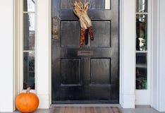 Porta preta com milho indiano e abóbora da queda Fotografia de Stock