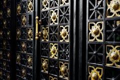 Porta preta velha do ferro com ornamento dourados Imagem de Stock Royalty Free