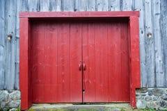 Porta rossa su un granaio di legno Immagine Stock