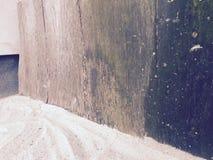 A porta Rotting encontra a parede e a areia Imagem de Stock Royalty Free