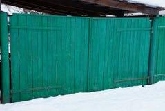 Porta rural de madeira verde na rua na neve branca fotografia de stock