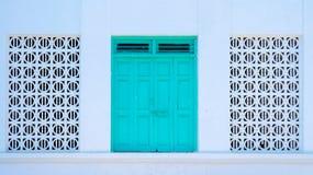 Porta tradicional flanqueada por janelas do teste padrão Fotografia de Stock