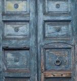 Porta velha azul com pintura rachada e um botão do vintage para bater na porta sob a forma de um anel imagem de stock royalty free