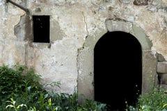 Porta velha da pedra da entrada e janela pequena na floresta imagem de stock