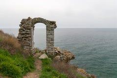 A porta velha do arco de Bulgária da fortaleza de Kaliakra através das virgens joga-se na legenda do mar imagem de stock royalty free