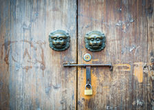 A porta velha do estilo chinês e o animal selvagem mítico dirigem o puxador da porta Imagens de Stock
