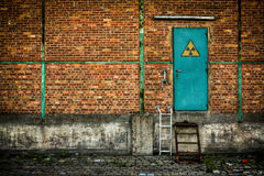 Porta verde com sinal nuclear na parede de tijolo Fotografia de Stock