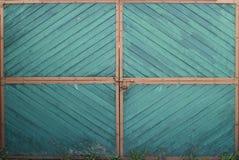 Porta verde de madeira da porta com cantos alaranjados e grama em uma terra fotografia de stock