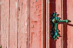 porta vermelha castigado pelo mau tempo velha com o botão de porta velho do vintage, superfície com pintura textured rachada fotos de stock royalty free