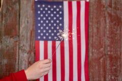 Porta vermelha do barnwood com bandeira americana e mão que guarda o chuveirinho - imagem de stock