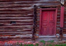 Porta vermelha em uma parede velha do log Foto de Stock Royalty Free
