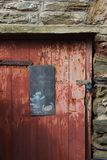 Porta vermelha velha cercada sobre pela pedra de Devon, Reino Unido Imagem de Stock
