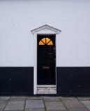 Porta vitoriano de madeira preta em uma parede preto e branco Imagem de Stock
