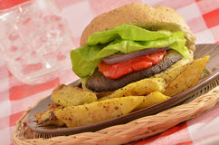 Portabella mushroom burger. Fresh grilled organic portabella mushroom burger on whole wheat bun with red pepper, red onion, lettuce and spicy wedge sweet potato Stock Photos