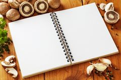 Portabello Mushroom Recipe. Portabello mushrooms and a notebook with blank pages for your recipe. Also includes garlic, peppercorns, parsley and thyme Royalty Free Stock Photo