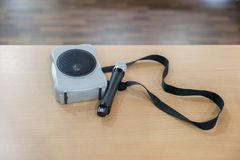 Portable amplifier speaker with microphone. On table Royalty Free Stock Photo