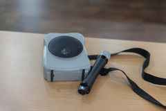 Portable amplifier speaker with microphone. On table Stock Images